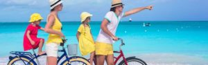 Family on bikes at the beach